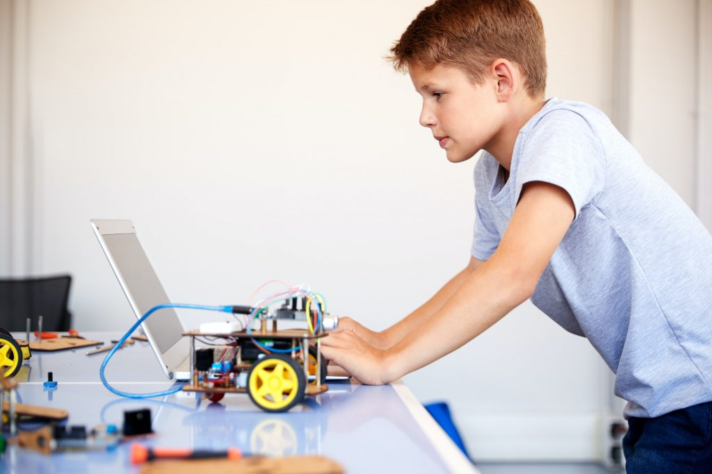 Male Student Building And Programing Robot Vehicle In School Computer Coding Class