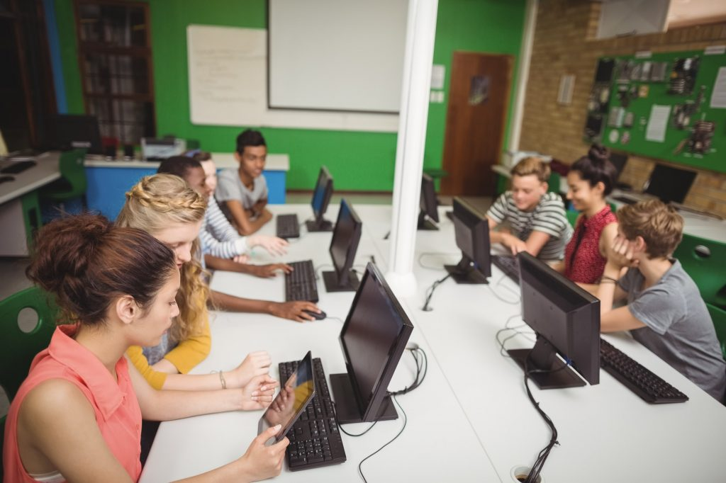 Smiling students studying in computer classroom