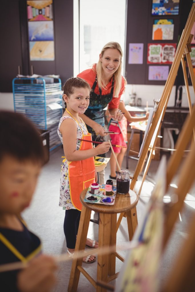 Teacher assisting girl in drawing class