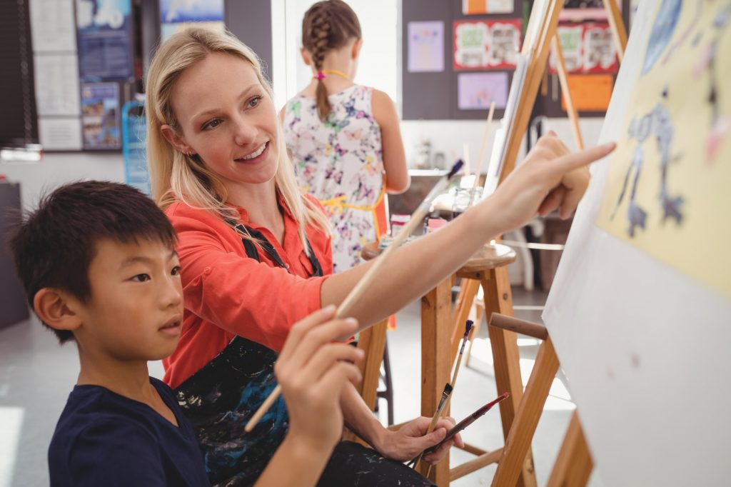 Teacher assisting schoolboy in drawing class